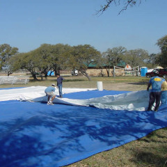 Lay out tarps to protect the tent top